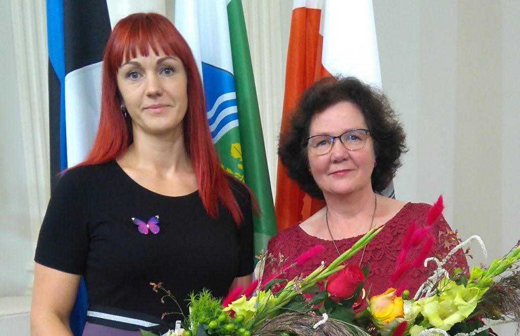 Kas naisõpetajat lillesülemitega. Taamal Eesti, Tartumaa ja Tartu linna lipp.